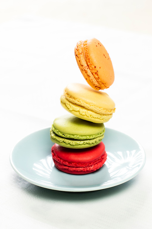 Falling macarons pastries on a seamless white background.