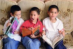 Group of boys sitting on sofa reading story books,