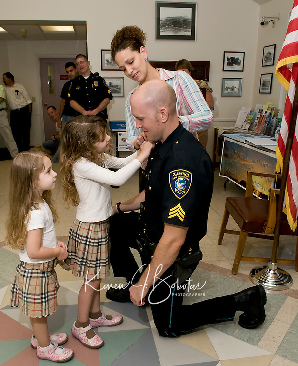 Sergeant Corey J. O'Connor gets assistance from his daughters Kaelan and Brenna along with his wife Diana to attach pins after O'Connors promotion ceremony at Gilford Town Hall Monday evening.  (Karen Bobotas/for the Laconia Daily Sun)