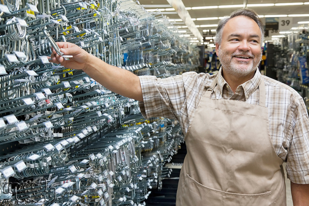 Happy mature salesperson holding metallic equipment while looking away in hardware store