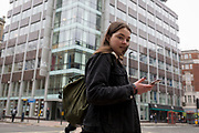 The day after Facebook's Mark Zuckerberg faced Senate Committee questions in Washington, a young woman uses her mobile phone outside the offices of Cambridge Analytica on New Oxford Street, the UK company accused of harvesting the personal details of Facebook users (including Zuckerberg himself) in its data privacy scandal, on 11th April, 2018, in London, England.