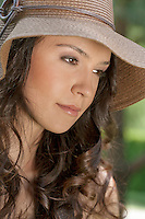 Thoughtful young woman wearing sunhat in park