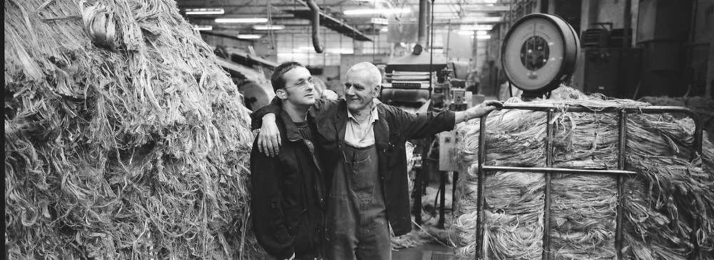 Two workers enjoying a joke together at Tay Spinners mill in Dundee, Scotland. This factory was the last jute spinning mill in Europe when it closed for the final time in 1998. The city of Dundee had been famous throughout history for the three 'Js' - jute, jam and journalism.