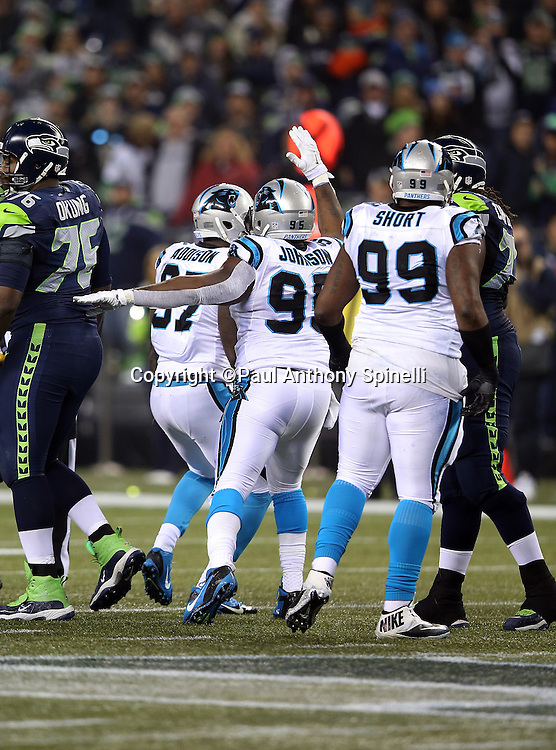 Carolina Panthers defensive tackle Kawann Short (99) looks on as Carolina Panthers defensive end Charles Johnson (95) and Carolina Panthers defensive end Mario Addison (97) celebrate after sacking Seattle Seahawks quarterback Russell Wilson (3) and forcing a third quarter punt during the NFL week 19 NFC Divisional Playoff football game against the Seattle Seahawks on Saturday, Jan. 10, 2015 in Seattle. The Seahawks won the game 31-17. ©Paul Anthony Spinelli