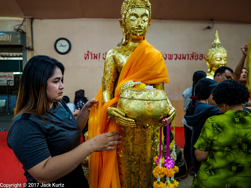 31 MAY 2017 - CHACHOENGSAO, THAILAND: A woman wraps a statue of the Buddha in orange cloth at Wat Sothon (also spelled Sothorn) in Chachoengsao, Thailand. The temple is one of the largest and most visited in Thailand. People make merit by paying to wrap the Buddha statues in orange robes. The temple is most famous because people leave hard boiled eggs as an offering at the temple. They ask for business success or children and leave hundreds of hard boiled eggs.      PHOTO BY JACK KURTZ