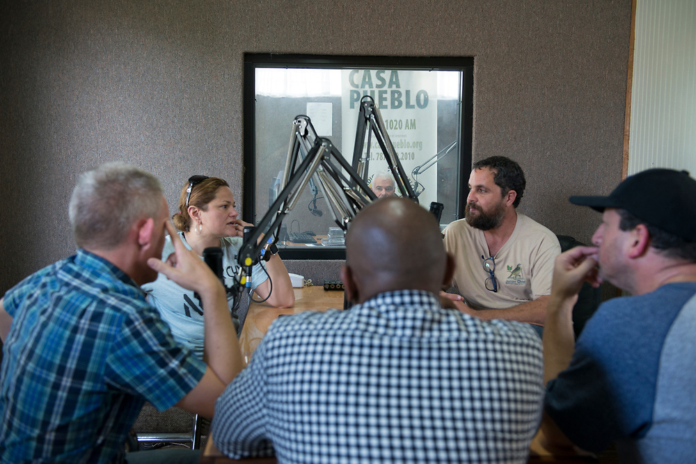 Adjuntas, PR, November 10, 2017--Arturo Massol Deyá, right, is the director of Casa Pueblo. Deyá interviews a New York delegation at Radio Casa Pueblo in Adjuntas, PR. Casa Pueblo is a community self-management project that is committed to the appreciation and protection of natural, cultural and human resources. It was founded in1980 to organize communities to protest proposed mining operations that would impact 36,000 acres of land in the municipalities of Adjuntas, Utuado, Lares and Jayuya. Since Hurricane Maria, Casa Pueblo has become a center for relief operations and ramped up the campaign @LightupPRcasapueblo that distributes and promotes the use of solar energy in Puerto Rico. Casa Pueblo has distributed over 6,000 solar lamps since the storm. Photo by Lori Waselchuk/braf.org