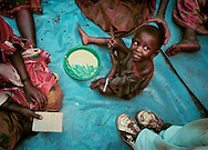 A young Hutu boy has a meal of porridge in a supplemental feeding program coordinated by the International Rescue Committee. Because of his poor nutritional health, he qualifies for the supplemental meal four times a day. The porridge consists of a blend of corn and soy flour, oil and sugar.