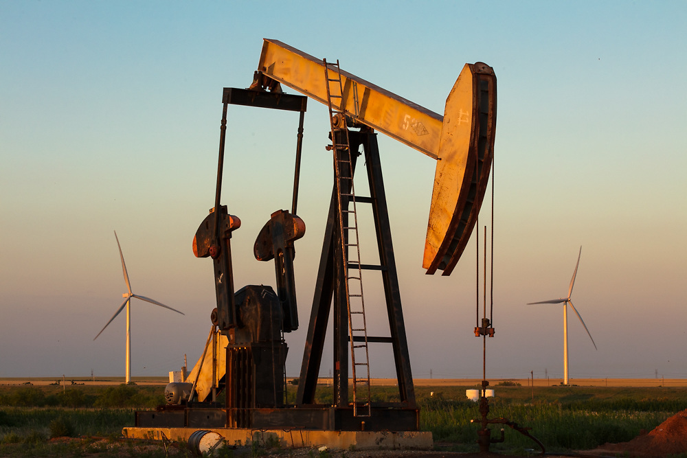 Pump jack and wind turbines in a rural Texas field at dusk.