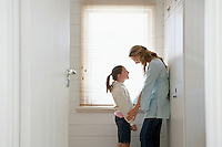 Mother and daughter standing face to face by window half length