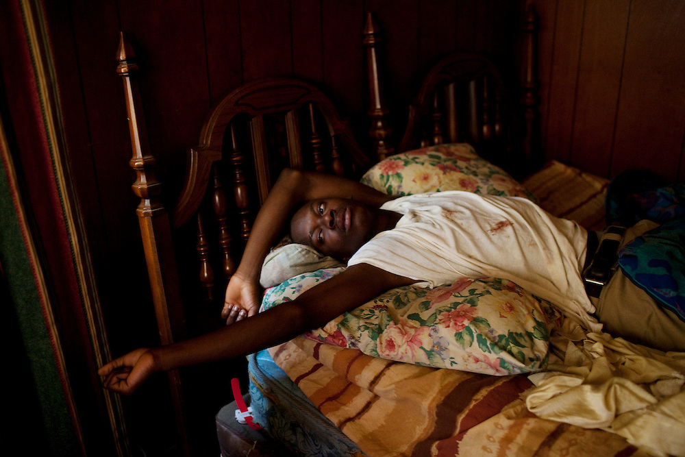 "Korwin ""Quan"" Wilson, 17, stretches as he awakes in his aunt Ellen ""El"" Wilson's bed in the Baptist Town neighborhood of Greenwood, Mississippi on Saturday, February 19, 2011. The night before she had to be taken to the hospital for medical complications and after returning to her house, Korwin fell asleep in her bed, his aunt on the sofa."