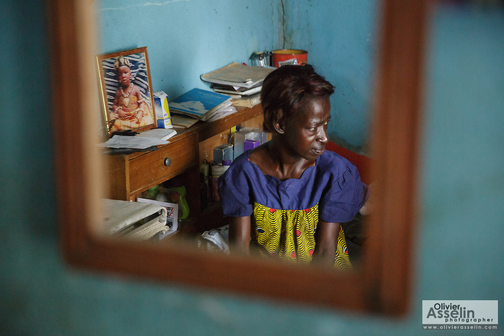 Adjua Yao, 45, who is HIV positive, is reflected in a mirror as she sits in a room of her sister's home in the Campement neighborhood of Abidjan, Cote d'Ivoire on Wednesday July 10, 2013. Adjua, a mother of five, is currently unemployed and lives with her sister. She's under ARV treatment and takes three pills a day.
