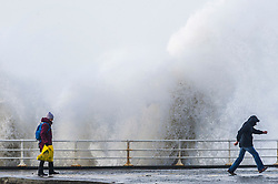 © London News Pictures. 01/02/2016. Aberystwyth, UK. <br /> Two walkers attempt to avoid being soaked by a large wave as storm Henry, the eighth named storm of the 2015/16 winter, batters the coast and sea defences at Aberystwyth in Wales.  Yellow and Amber severe weather warnings are in place for much of northern England and Scotland. Photo credit: Keith Morris/LNP