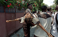 A young woman injured in street rioting is carried away in Port-au-Prince, Haiti, May 1995. (Photo by Roger M. Richards)