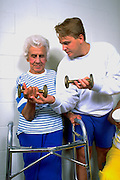 Trainer & Woman with walker age 25 and age 80 lifting weights at Lynnwood Recreation Center.  St Paul Minnesota USA