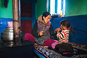 A Spiti mother and a child interact in their kitchen in Langza village of Spiti