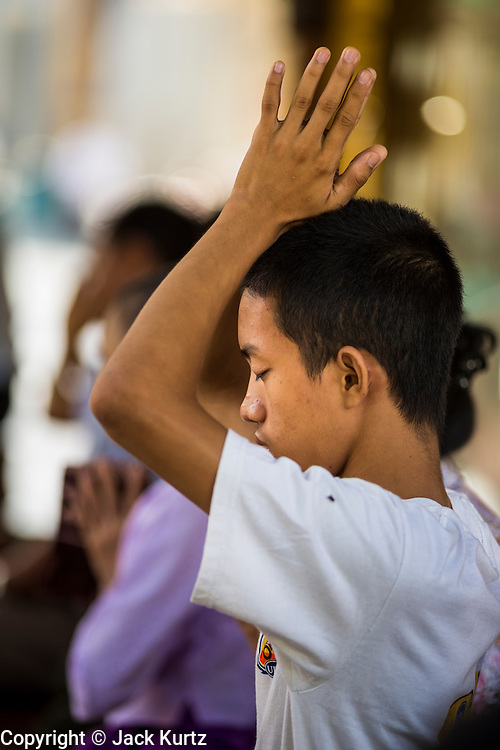 07 JUNE 2014 - YANGON, YANGON REGION, MYANMAR: A man prays at Shwedagon Pagoda in Yangon (Rangoon), Myanmar (Burma). Shwedagon Pagoda is officially called Shwedagon Zedi Daw and is also known as the Great Dagon Pagoda and the Golden Pagoda. It's a 99 metres (325ft) gilded pagoda and stupa located in Yangon. It is the most sacred Buddhist pagoda in Myanmar with relics of the past four Buddhas enshrined within: the staff of Kakusandha, the water filter of Koṇāgamana, a piece of the robe of Kassapa and eight strands of hair from Gautama, the historical Buddha.   PHOTO BY JACK KURTZ