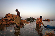 A man and his son search through the rubble of their destroyed home for any possessions they can salvage, in Jhanghara, Sindh province, Pakistan