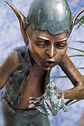 A copper-toned elf converses with a frog on his hand in this garden sculpture.