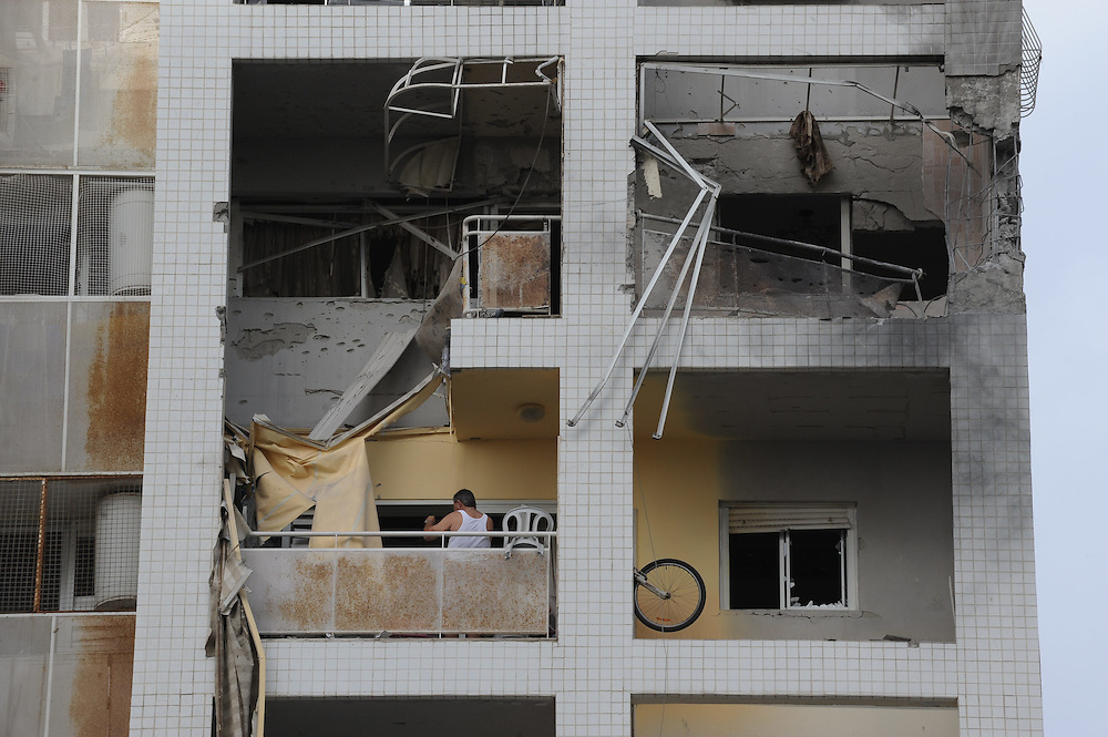 Ashdod, Israel - November 17, 2012: A man stands at his on a balcony of a building that was hit by a rocket fired from Gaza Strip, at the fourth day of Operation Pillar of Defense. Photo by Gili Yaari
