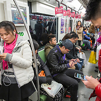 China, Shanghai, Young adults texting and playing games on mobile phones aboard Shanghai Metro subway train