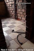 A cell and chains used by the Khmer Rouge to shackle prisoners to the wall during the Pol Pot regime are depicted in a building at Tuol Sleng Genocide Museum in Phnom Penh, Cambodia. The building contains several rows of very small cubicles that were used for detention and deprivation.
