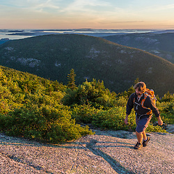 A man hiking on Cadillac Mountain in Maine's Acadia National Park.