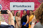 Girls pose for photographs prior to the MacMillan Charity Raceday held at York Racecourse, York, United Kingdom on 15 June 2019.