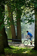 Een man fietst in het park in Utrecht.<br /> <br /> A man on a mountainbike is cycling in a park in Utrecht.