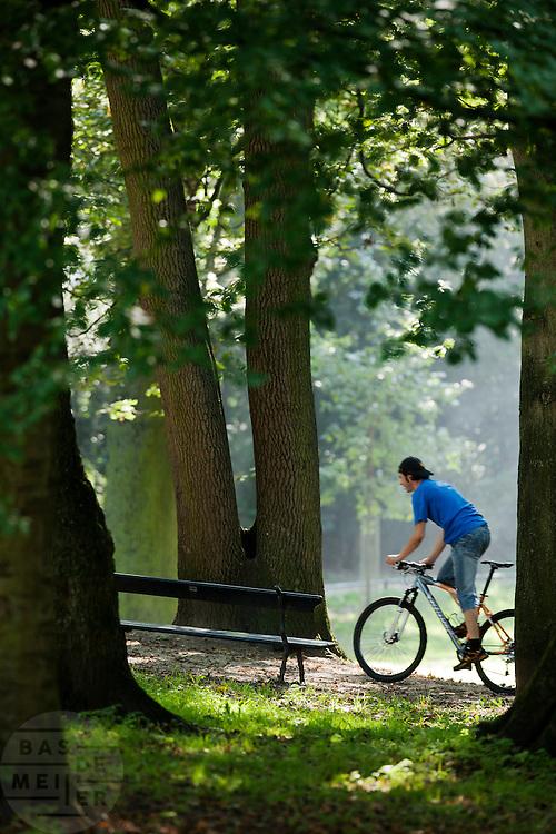 Een man fietst in het park in Utrecht.<br /> <br /> A man on a mountainbike is cycling in a park in Utrecht.