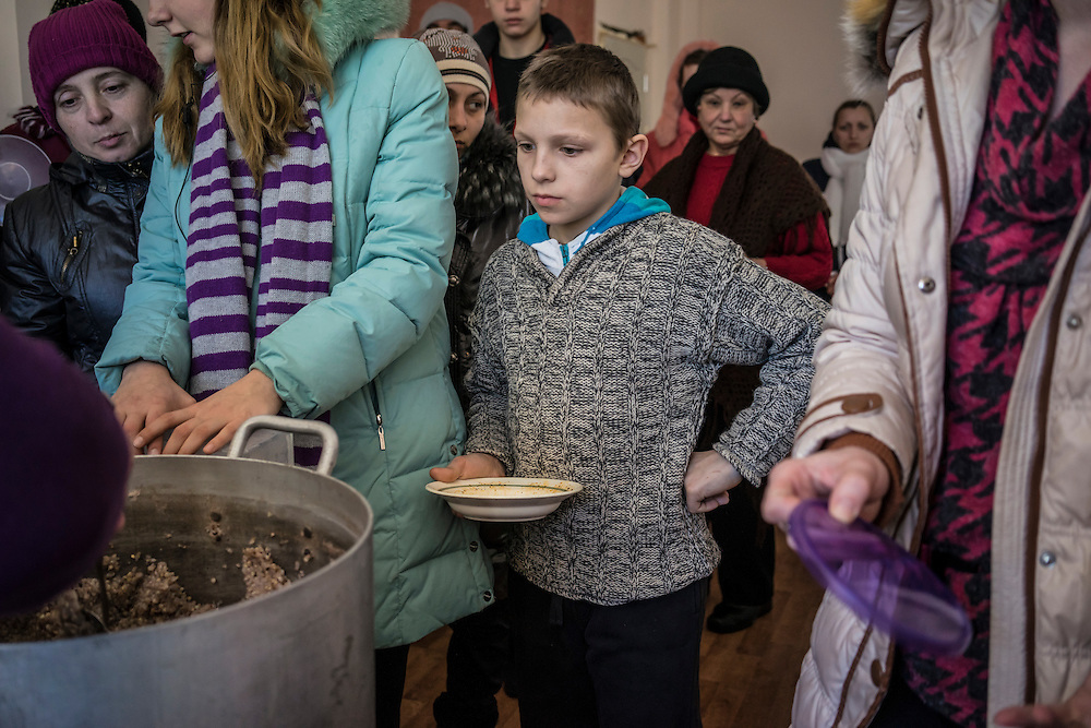 People displaced by fighting in Eastern Ukraine line up for lunch at the sanatorium where they're living on the city outskirts on Thursday, February 12, 2015 in Kharkiv, Ukraine.