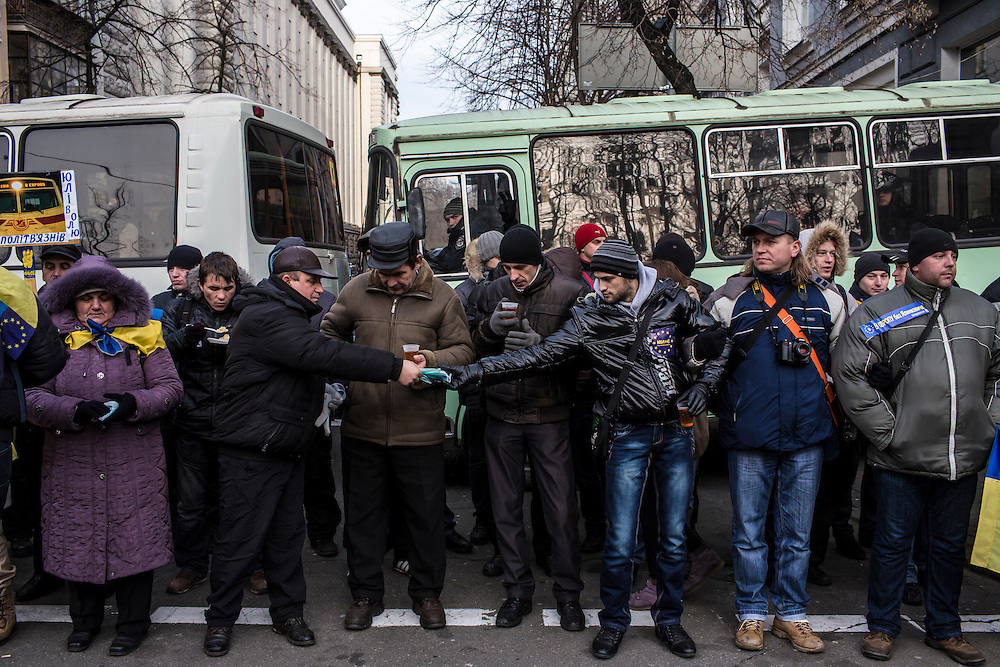 Anti-government protesters pass medical masks while blocking a street near several key government buildings. Protesters have put a focus on keeping healthy to keep up strength for their round-the-clock occupation of central Kiev.