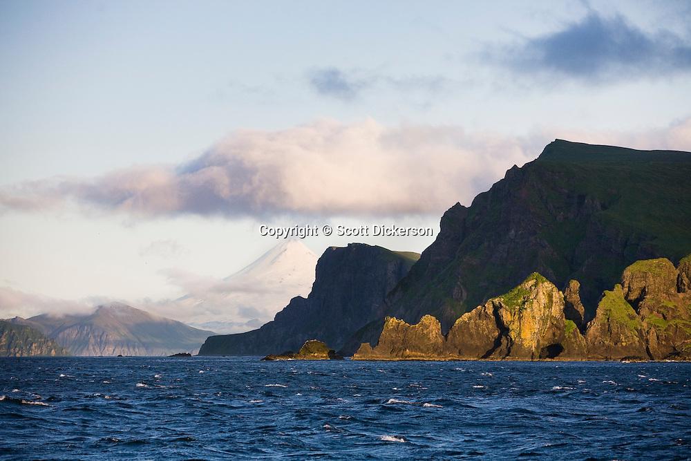 Shishaldin Volcano and rugged cliff shoreline on Unimak Island, Eastern Aleutian Islands, Alaska