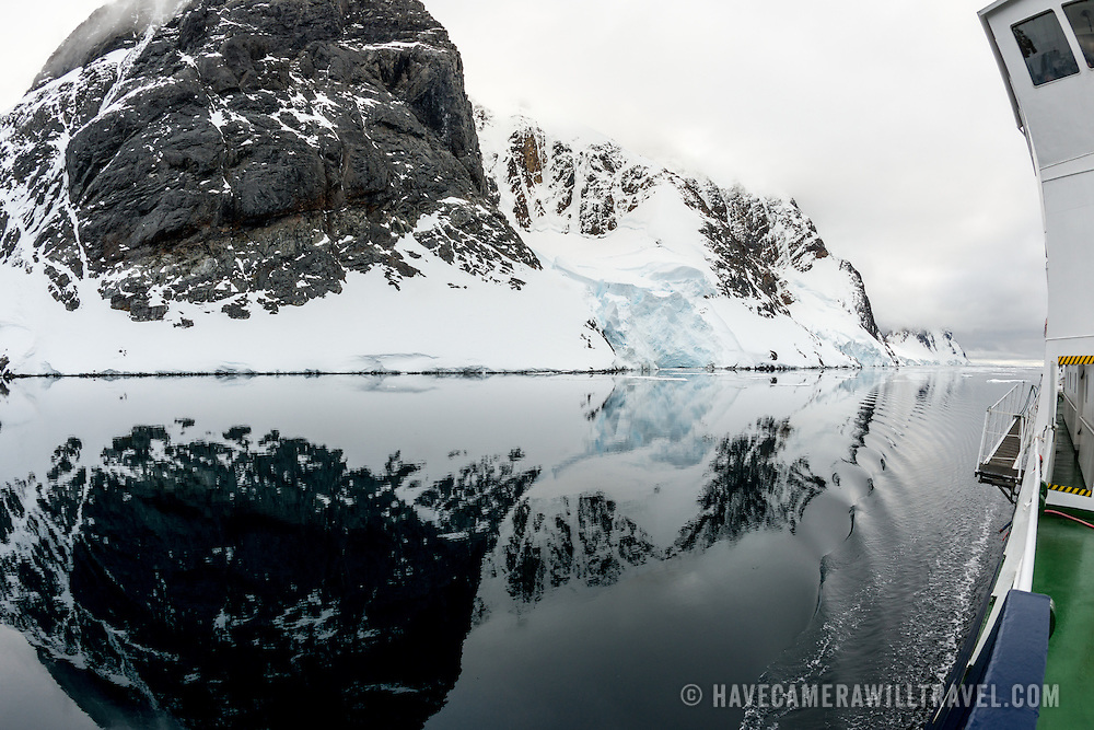 "An Antarctic cruise ship passes through glassy waters of the Lemaire Channel, as the mountains along the shore are reflected on the water. The Lemaire Channel is sometimes referred to as ""Kodak Gap"" in a nod to its famously scenic views. At right can be seen part of a cruise ship."