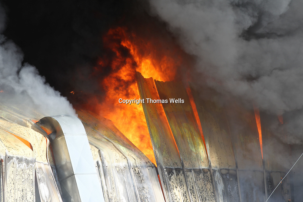 The fire begins to melt the wrp the metal siding of the southern wall of the American Furniture plant in Ecru Friday.