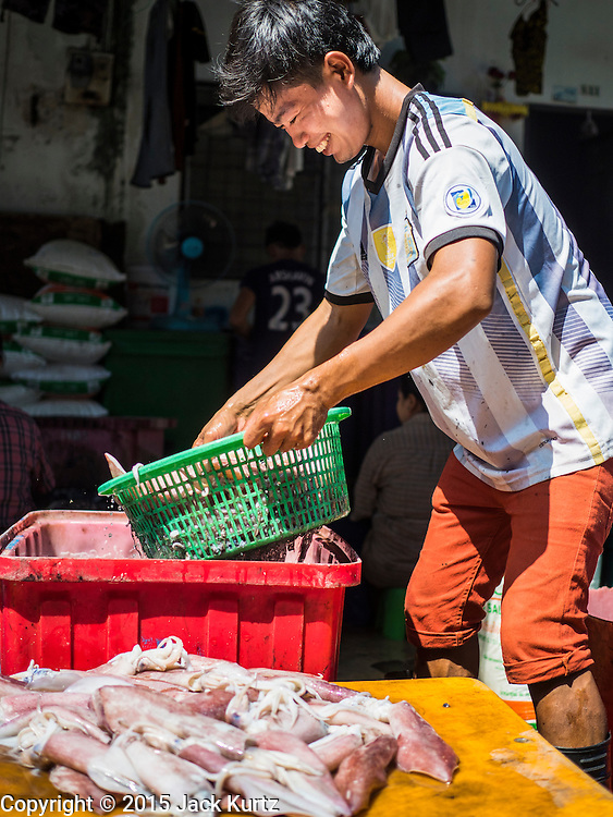 """11 JUNE 2015 - MAHACHAI, SAMUT SAKHON, THAILAND:  A Burmese migrant worker at the Samut Sakhon shrimp market in Mahachai cleans and sorts squid. Labor activists say there are about 200,000 migrant workers from Myanmar (Burma) employed in the fishing and seafood industry in Mahachai, a fishing port about an hour southwest of Bangkok. Since 2014, Thailand has been a Tier 3 country on the US Department of State Trafficking in Persons Report (TIPS). Tier 3 is the worst ranking, being a Tier 3 country on the list can lead to sanctions. Tier 3 countries are """"Countries whose governments do not fully comply with the minimum standards and are not making significant efforts to do so."""" After being placed on the Tier 3 list, the Thai government cracked down on human trafficking and has taken steps to improve its ranking on the list. The 2015 TIPS report should be released in about two weeks. Thailand is hoping that its efforts will get it removed from Tier 3 status and promoted to Tier 2 status.       PHOTO BY JACK KURTZ"""