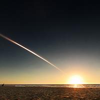 Seascape with people on Busselton Beach, Australia with setting sun on horizon