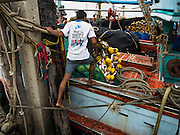 01 OCTOBER 2015 - MAHACHAI, SAMUT SAKHON, THAILAND:   A crewman climbs onto a fishing trawler in Mahachai, one of Thailand's largest fishing ports. Thailand's fishing industry had been facing an October deadline from the European Union to address issues related to overfishing and labor practices. Failure to adequately address the issues could have resulted in a ban on Thai exports to the EU. In September Thai officials announced that they had secured an extension of the deadline. Officials did not say how much extra time they had to meet the EU goals. Thailand's overall annual exports to the EU are between 23.2 billion Thai Baht and 30 billion Thai Baht (US$645 million to US $841 million). Thailand's total fish exports were worth about 110 billion baht in 2014.   PHOTO BY JACK KURTZ