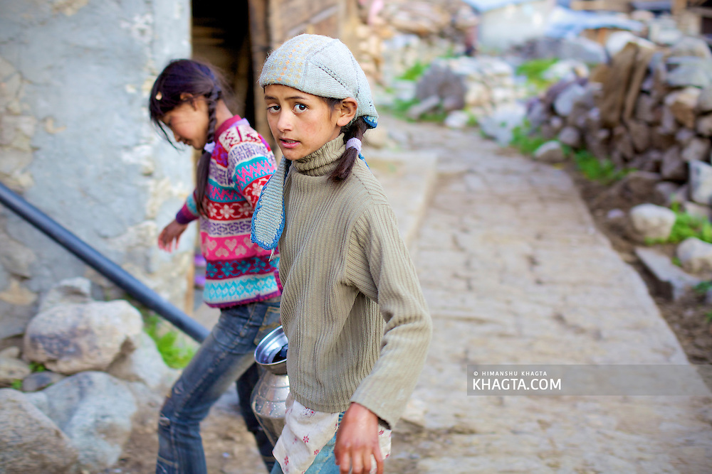 Two little girls of Chitkul carrying water to their houses. <br /> <br /> The rural village of Chitkul has a common water source from where the village collects water everyday. The chilled water from the glaciers is consumed without any sort of purification.