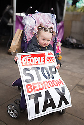 © Licensed to London News Pictures . 16/03/2013 . Manchester , UK . A child in a pushchair holds a STOP BEDROOM TAX poster . Hundreds of protesters opposed to changes to housing benefit , known as the Bedroom Tax , in Piccadilly Gardens in Manchester City Centre today (16th March) as part of a coordinated campaign of demonstrations in cities across the UK . The government plans to introduce changes to housing benefit from this April which will see some claimants receive a reduced amount if they have excess living space . Photo credit : Joel Goodman/LNP