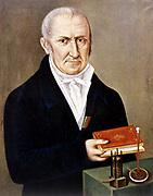 Alessandro Volta (1745-1827) Italian physicist. On table are two of his inventions, the Voltaic pile (wet battery) on left,  and electrophorus, an apparatus demonstrating electrostatic charge by induction. His name given to unit of electrical potential difference, Volt.