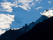 The sunrise shadow of Aiguille du Midi (3842 meters or 12,605 feet) makes a pyramid in clouds above Chamonix, France, the Alps, Europe. Aiguille du Midi téléphérique is the highest vertical ascent cable car in the world, from 1035 meters to 3842 m.
