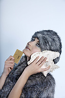 studio shot portrait of a beautiful woman russian type in a fur coat and hat holding a credit card and listening to the sea through ashell