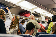 Airline travelers retrieve their carry-on luggage from overhead compartments.