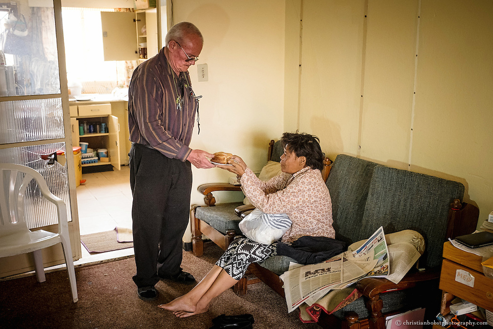 (2013)  Father Hermann offers slices of bread and butter to a woman who seeks his help at his home at the church in Pioneers Park.