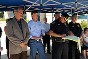 Aurora CO 21 July 2012: LEFT to Right- Aurora Mayor (tan sportcoat), CO's Governor Hickenlooper (C) and Aurora's Chief of Police stand somberly in the shade at press conference listening to an FBI official.