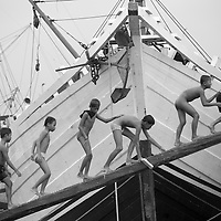 Indonesia, Jakarta, Young boys playing outside wooden boats moored at Old Harbor at Sunda Kelapa