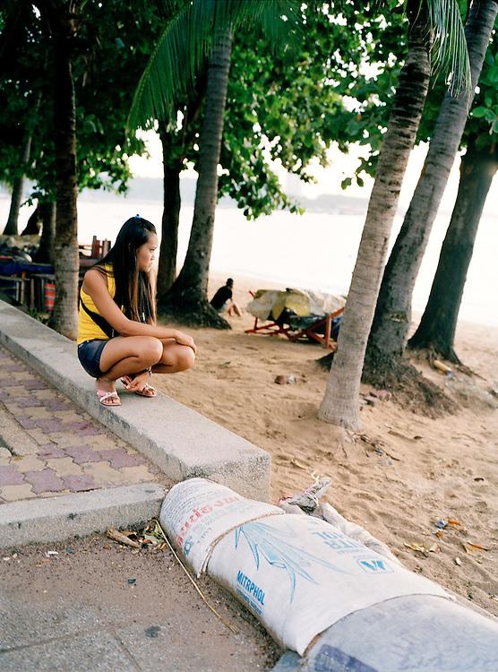 A woman gazes out to sea on Pattaya beach.