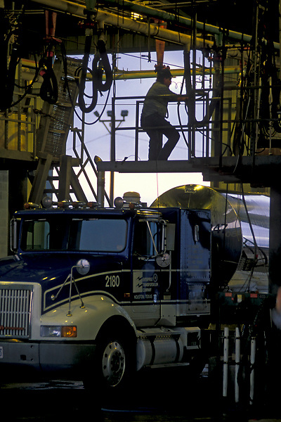 Men working in a maintenance garage working on a large liquid transport truck preparing it for delivery
