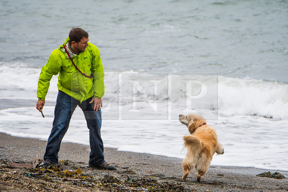 © London News Pictures. 14/04/2017 Aberystwyth, UK.<br /> A man walking his dog on the seafront on a dreary, cold grey and damp Good Friday morning in Aberystwyth on the Cardigan Bay coast of west Wales UK at the start of the Easter Bank Holiday weekend. Photo credit: Keith Morris/LNP