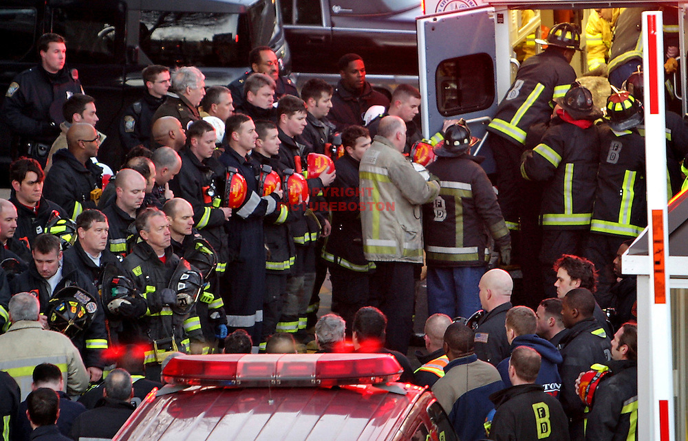 Boston Firefighters stand at attention as the corpse of a firefighter is finally removed from the rubble of a day care center after the fire truck he was riding crashed into the building.